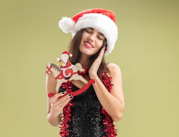 Erfreut mit geschlossenen augen, junges schönes mädchen mit weihnachtsmütze mit girlande am hals, das weihnachtsspielzeug hält, das hand auf die wange legt, isoliert auf olivgrünem hintergrund