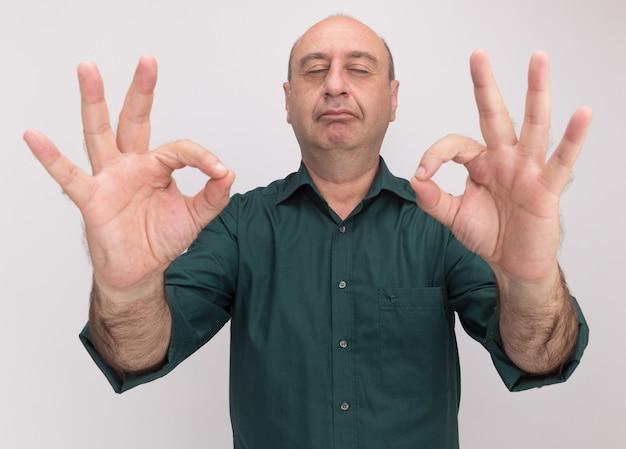 Erfreut mit geschlossenen augen, mann mittleren alters, der ein grünes t-shirt trägt, das isoliert auf weißer wand meditiert