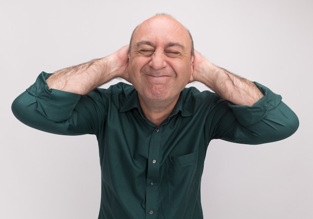 Erfreut mit geschlossenen augen, mann mittleren alters, der ein grünes t-shirt trägt und die hände hinter den kopf legt, isoliert auf weißer wand