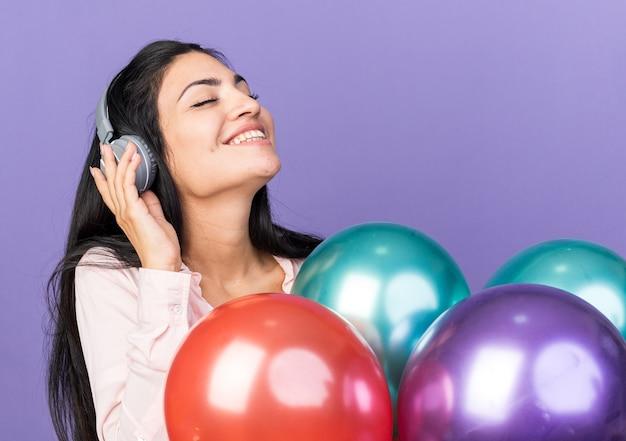 Erfreut mit geschlossenen augen mit kopfhörern junges schönes mädchen mit ballons