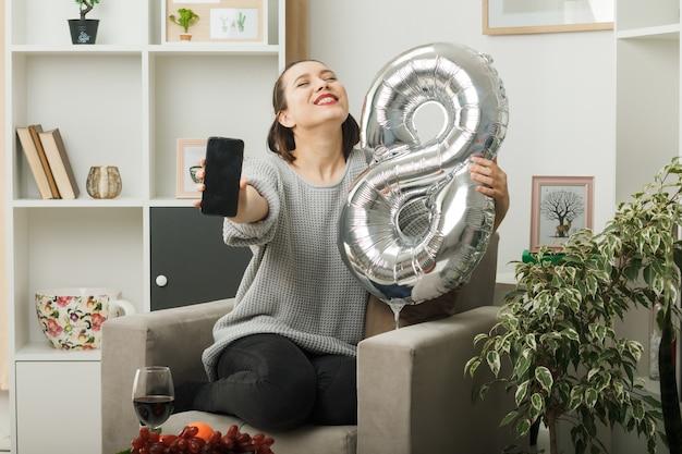 Erfreut mit geschlossenen augen schöne frau am glücklichen frauentag, der den ballon nummer acht mit dem telefon hält, das auf einem sessel im wohnzimmer sitzt