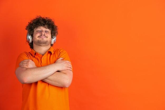 Erfreut musik hören. das monochrome portrait des kaukasischen jungen mannes an der orangefarbenen wand. schönes männliches lockiges modell im lässigen stil. konzept der menschlichen emotionen, gesichtsausdruck,.