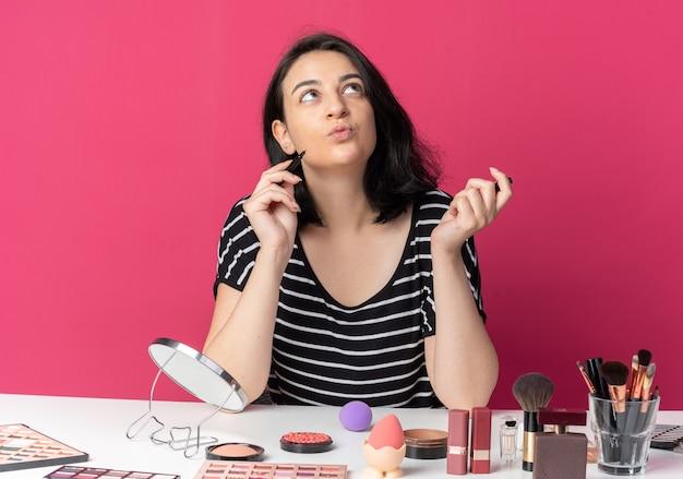 Erfreut nachschlagendes junges schönes mädchen sitzt am tisch mit make-up-tools, die eyeliner isoliert auf rosa wand halten