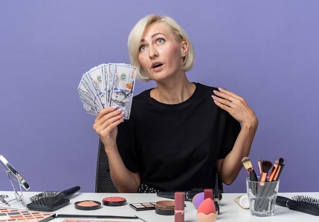 Erfreut nachschlagendes junges schönes mädchen sitzt am tisch mit make-up-tools und hält bargeld isoliert auf blauer wand