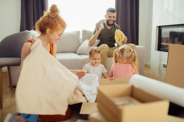 Erfreut nette familie, die ihre kisten zusammen auspackt