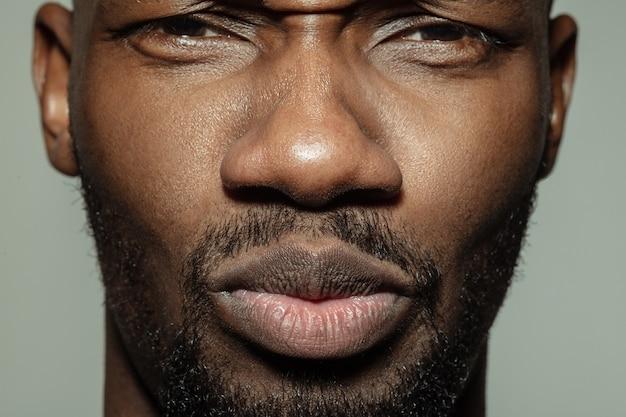 Erfreut, ruhig. nahaufnahme des gesichts des schönen afroamerikanischen jungen mannes, fokus auf den mund.
