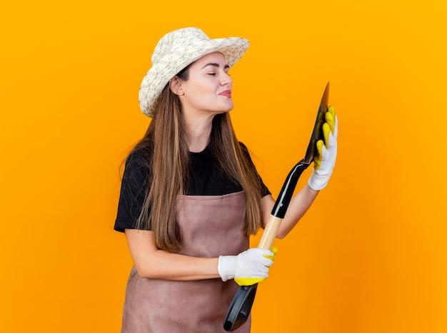 Erfreut schönes gärtnermädchen, das uniform und gartenhut mit handschuhen hält, die spaten lokalisiert auf orange hintergrund halten und betrachten