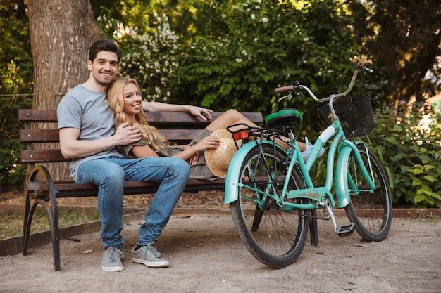 Erfreut schönes junges paar, das zusammen auf bank mit fahrrad im freien entspannt