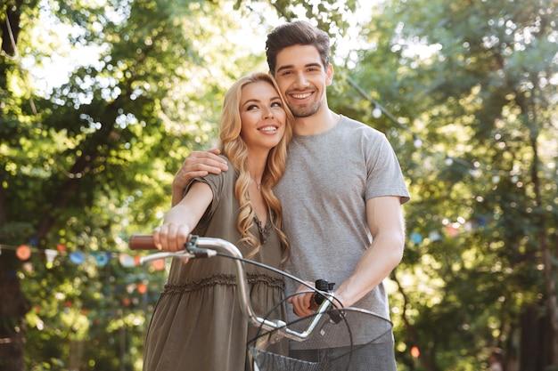 Erfreut schönes junges paar, das zusammen mit fahrrad aufwirft