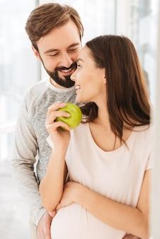 Erfreut schwangeres junges paar umarmt