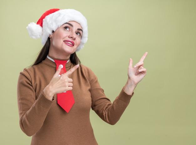 Erfreut, seitliches junges schönes mädchen, das weihnachtshut mit medizinischen maskenpunkten an der seite trägt, lokalisiert auf olivgrünem hintergrund