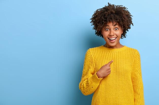 Erfreut überraschte frau mit einem afro, der in einem rosa pullover posiert