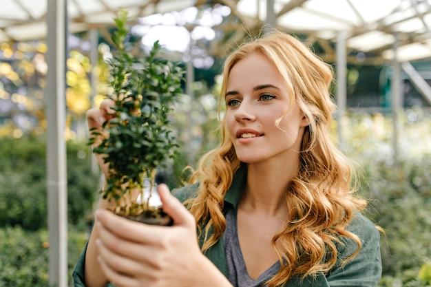 Erfreut untersucht der forscher die struktur der pflanze. junge frau in der grünen spitze niedlich lächelnd, die für porträt aufwirft.