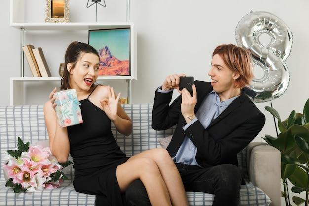 Erfreut zeigt ein junges paar in ordnung, das am glücklichen frauentag mädchen hält, das den anwesenden kerl hält, und machen sie ein foto, das auf dem sofa im wohnzimmer sitzt