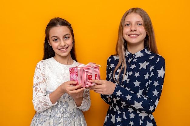 Erfreut zwei kleine mädchen, die ein geschenk isoliert auf einer orangefarbenen wand halten