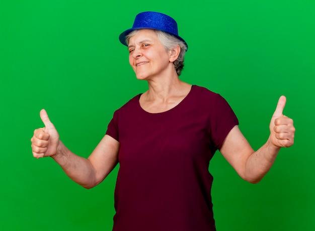 Erfreute ältere frau, die partyhut daumen hoch mit zwei händen auf grün trägt