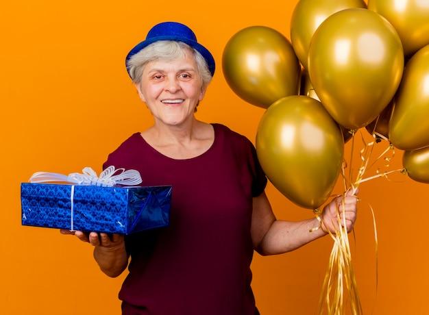 Erfreute ältere frau, die partyhut trägt, hält heliumballons und geschenkbox auf orange