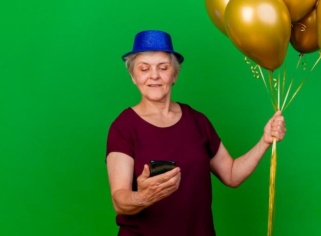 Erfreute ältere frau, die partyhut trägt, hält heliumballons und schaut telefon auf grün