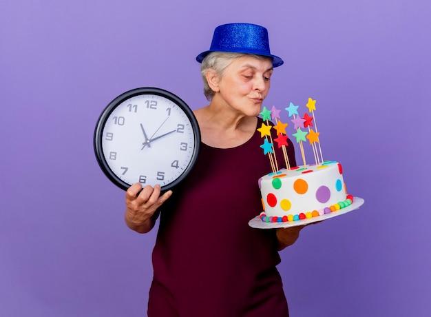 Erfreute ältere frau, die partyhut trägt, hält uhr und schaut auf geburtstagstorte lokalisiert auf lila wand mit kopienraum