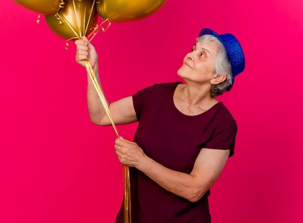 Erfreute ältere frau, die partyhut trägt, hält und betrachtet heliumballons auf rosa