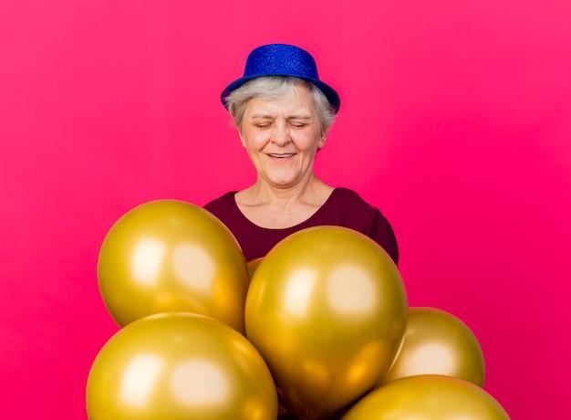 Erfreute ältere frau, die partyhut trägt, steht mit heliumballons auf rosa