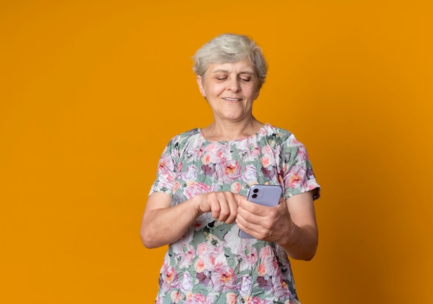Erfreute ältere frau, die telefon lokalisiert auf orange wand hält und betrachtet
