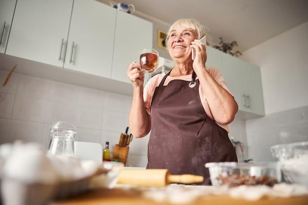 Erfreute ältere frau, die zu hause telefongespräche führt