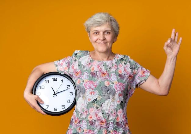 Erfreute ältere frau gestikuliert ok handzeichen, das uhr auf orange wand lokalisiert hält