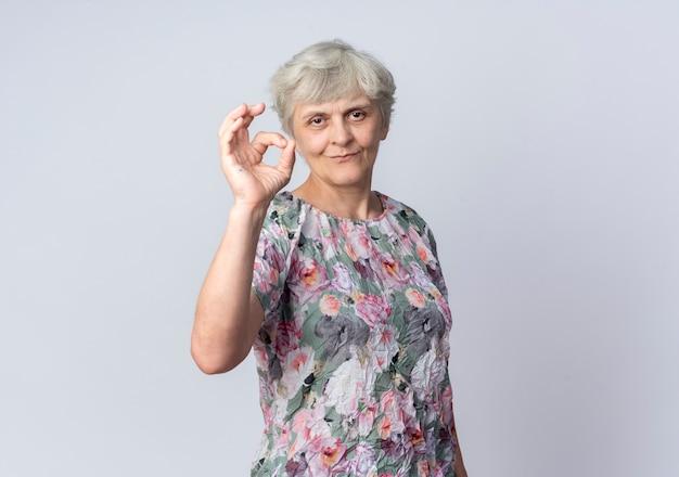 Erfreute ältere frau gestikuliert ok handzeichen lokalisiert auf weißer wand
