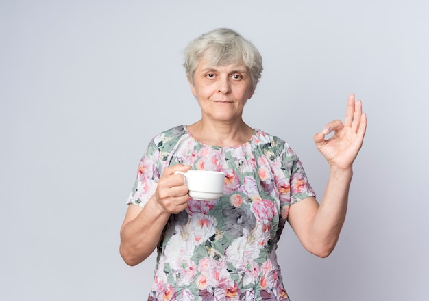 Erfreute ältere frau hält tasse und gestikuliert ok handzeichen lokalisiert auf weißer wand