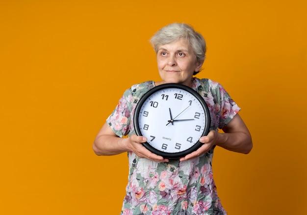Erfreute ältere frau hält uhr, die seite betrachtet, die auf orange wand lokalisiert ist