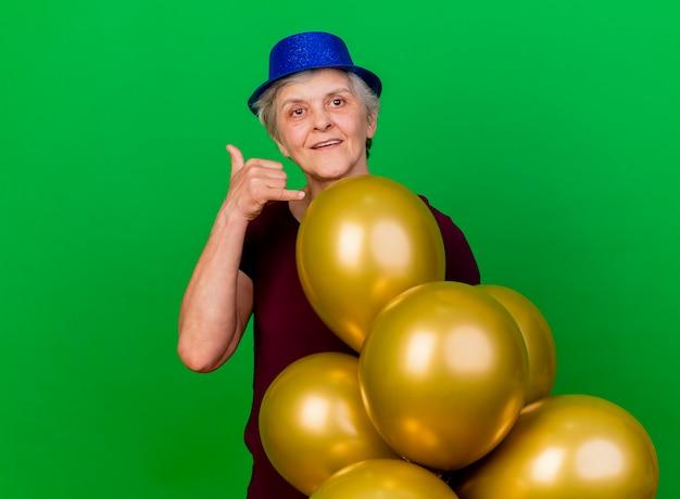 Erfreute ältere frau mit partyhut steht mit heliumballons gestikulierend, ruf mich zeichen auf grün an