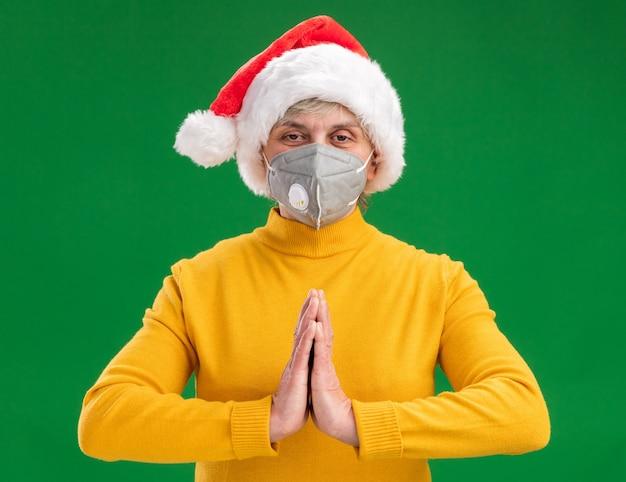 Erfreute ältere frau mit weihnachtsmütze, die medizinische maske hält, die hände zusammen lokalisiert auf grünem hintergrund mit kopienraum trägt