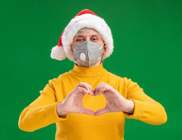 Erfreute ältere frau mit weihnachtsmütze, die medizinisches masken gestikulierendes herzzeichen trägt, lokalisiert auf grünem hintergrund mit kopienraum