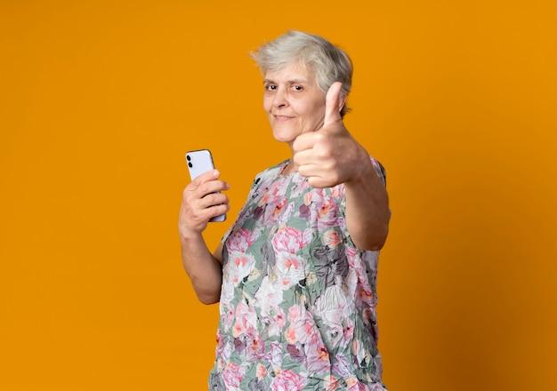 Erfreute ältere frau steht seitlich und hält telefon und daumen isoliert auf orange wand