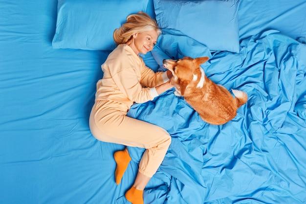 Erfreute alte europäische frau in nachtwäsche spielt mit lieblingshaustier zu hause im schlafzimmer zusammen im bett liegen genießen guten tag. frauen mittleren alters drücken liebe und fürsorge für den hund als familienmitglied aus