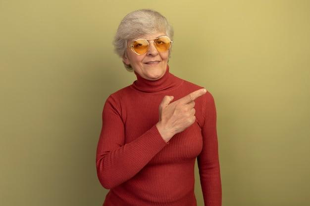 Erfreute alte frau mit rotem rollkragenpullover und sonnenbrille, die auf die seite zeigt, isoliert auf olivgrüner wand mit kopierraum