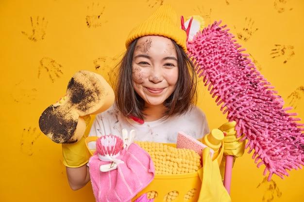 Erfreute asiatische frau hat freude am reinigungsprozess hält schmutzigen schwamm und mopp in der nähe eines korbes voller wäsche isoliert über gelber wand