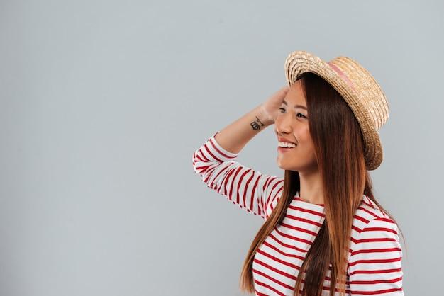 Erfreute asiatische frau in pullover und hut schaut weg