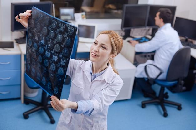 Erfreute attraktive ärztin, die in ihrem labor steht und die röntgenbilder betrachtet, während sie in einer positiven stimmung ist