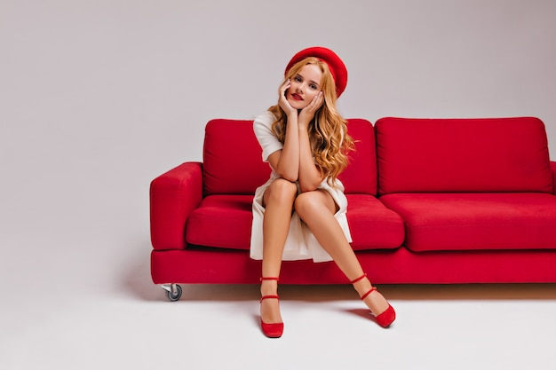 Erfreute attraktive kaukasische frau in den roten schuhen, die im wohnzimmer aufwerfen. entzückendes mädchen mit gewelltem haar, das auf kutsche sitzt und ihr gesicht berührt.