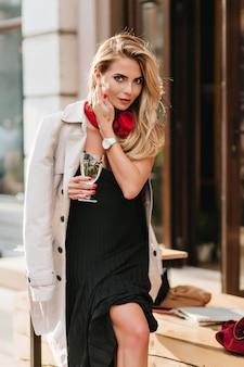 Erfreute blonde frau im langen schwarzen kleid, das mit haaren spielt und lächelt und glas champagner hält. attraktives mädchen im stilvollen mantel, der auf der straße neben kneipe steht und urlaub feiert.