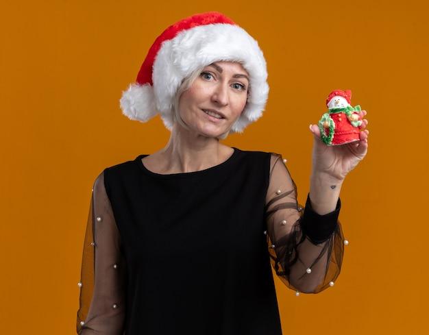 Erfreute blonde frau mittleren alters, die weihnachtsmütze trägt kamera betrachtet, die kleine schneemannstatue zur kamera lokalisiert auf orange hintergrund zeigt