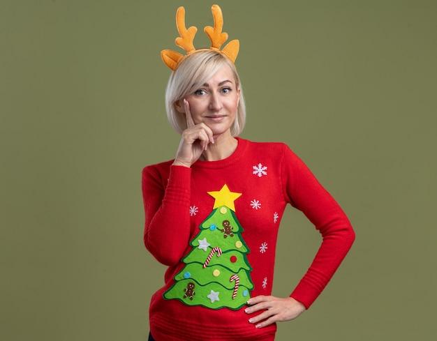 Erfreute blonde frau mittleren alters mit weihnachtsrentiergeweih-stirnband und weihnachtspullover, die hand auf taille und kinn hält, isoliert auf olivgrüner wand mit kopierraum