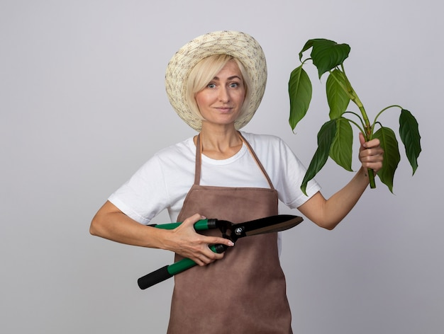 Erfreute blonde gärtnerin mittleren alters in uniform mit hut, die pflanze und heckenschere isoliert auf weißer wand hält