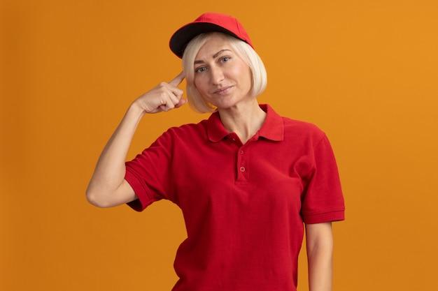 Erfreute blonde lieferfrau mittleren alters in roter uniform und mütze, die denkgeste isoliert auf oranger wand macht