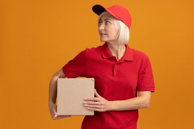 Erfreute blonde lieferfrau mittleren alters in roter uniform und mütze mit karton mit blick auf die seite isoliert auf oranger wand