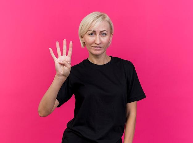 Erfreute blonde slawische frau mittleren alters, die front betrachtet, die vier mit der hand lokalisiert auf rosa wand mit kopienraum zeigt