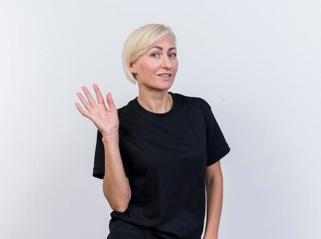 Erfreute blonde slawische frau mittleren alters, die kamera betrachtet und lokalisiert auf weißem hintergrund mit kopienraum winkt