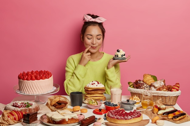 Erfreute brünette frau hält kleine cremige muffins, backt viele desserts für neujahrsferien oder festtage, zeigt ihre kulinarischen fähigkeiten